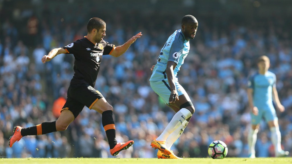 MAN IN THE MIDDLE: Yaya glances over his shoulder to keep an eye on where Evandro is.