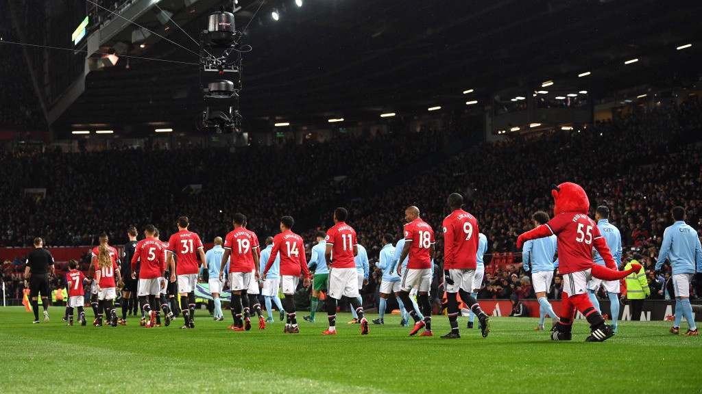 UNDER THE LIGHTS: The sides walk out at a wintry Old Trafford.